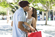 Happy young couple with shopping bag kissing - ZEF13419