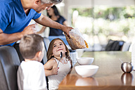 Father preparing cereal breakfast with kids - ZEF13424
