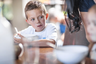 Boy eating breakfast at table - ZEF13427