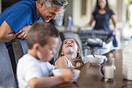 Happy family enjoying breakfast at table - ZEF13430