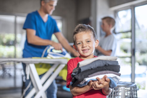 Smiling boy helping with chores holding folded clothes - ZEF13436