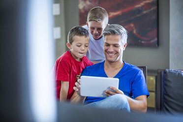 Children looking with their father on digital tablet - ZEF13445