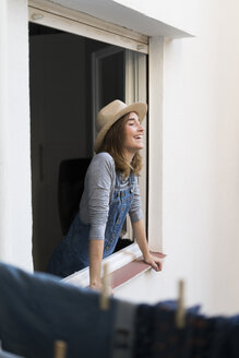 Happy young woman looking out of window - KKAF00582