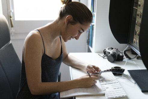 Female photographer editing images at desk - KKAF00591