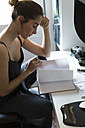 Young woman at desk looking in notebook - KKAF00594