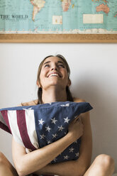 Smiling young woman holding US cushion under world map - KKAF00618