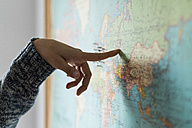 Woman's hand pointing on world map - KKAF00624