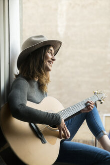Smiling young woman sitting in window frame playing guitar - KKAF00636