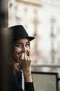 Portrait of smiling young woman wearing a hat - KKAF00639