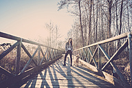 Woman standing on bridge with her dog - SIPF01500