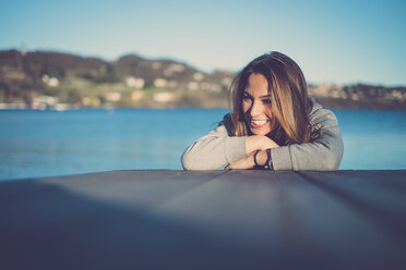 Portrait of a smiling woman at a lake - SIPF01503