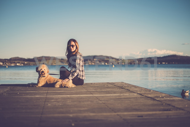 Woman sitting on jetty with her dog - SIPF01506 - Simona Pilolla/Westend61
