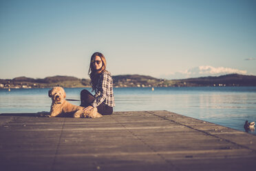 Woman sitting on jetty with her dog - SIPF01506