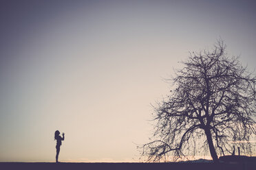 Silhouette of a woman practicing yoga in nature - SIPF01512