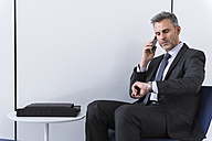 Businessman talking on the phone and checking the time - DIGF01552