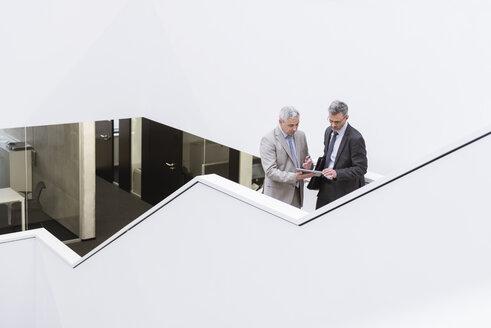 Two businessmen having an informal meeting, using digital tablet - DIGF01573