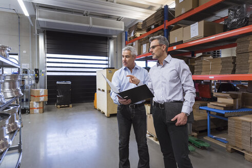 Two businessmen in factory hall talking - DIGF01579