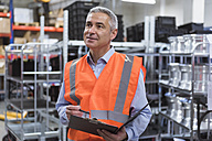 Man in factory hall wearing safety vest holding clipboard - DIGF01594