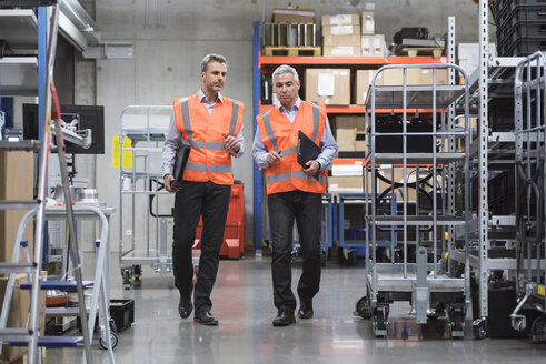 Two colleagues walking in factory hall wearing safety vests - DIGF01597
