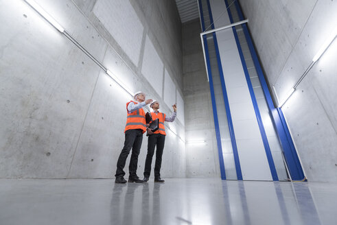 Two colleagues wearing safety vests and hard hats talking in a building - DIGF01600