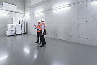 Two colleagues wearing safety vests and hard hats talking in a building - DIGF01603