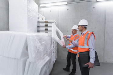 Two colleagues wearing safety vests and hard hats examining polystyrene - DIGF01606