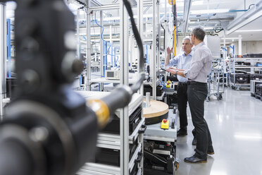 Two businessmen in modern factory hall talking - DIGF01615