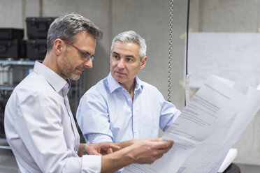 Two businessmen in factory hall discussing construction plan - DIGF01624