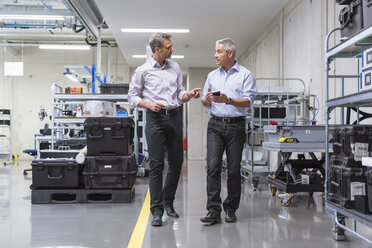 Two businessmen walking in factory hall - DIGF01633