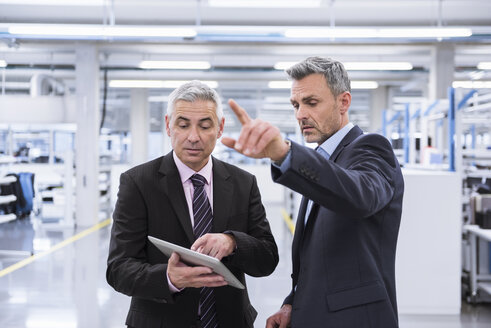 Two mangagers having a meeting at the shop floor of a factory - DIGF01636