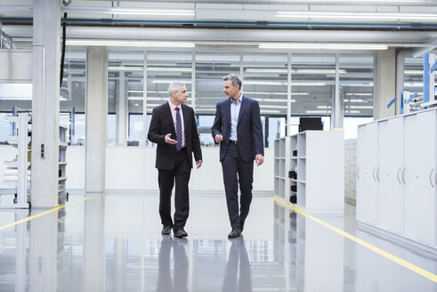 Two mangagers having a meeting at the shop floor of a factory - DIGF01639