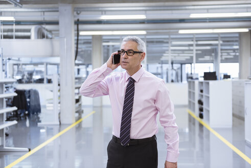 Manager on shop floor of a factory using smart phone - DIGF01654