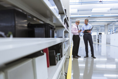 Two mangers discussing on shop floor of company - DIGF01657