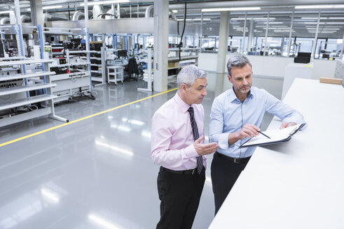 Two mangers discussing on shop floor of company - DIGF01672