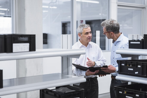Two managers with files standing in comany, discussing - DIGF01690