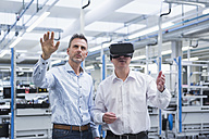 Two managers standing in company, using VR goggles - DIGF01699