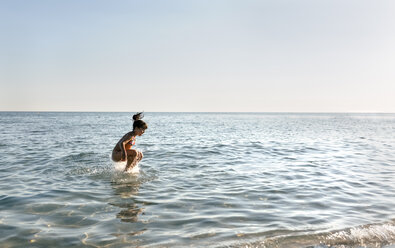 Spain, Menorca, girl jumping in the sea - MGOF03157