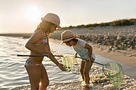 Spain, Menorca, two girls with dip nets on the beach - MGOF03166