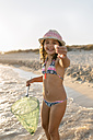 Spain, Menorca, portrait of happy girl with a dip net on the beach - MGOF03169