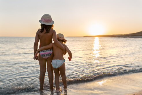 Spain, Menorca, two girls watching the sunset on the beach - MGOF03175