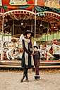 Happy young woman and little girl standing in front of children's carousel at fair - CHAF01808