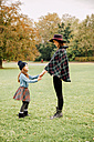 Young woman and little girl standing face to face on a meadow in autumn holding hands - CHAF01811