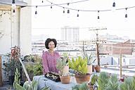 Smiling woman standing in her rooftop garden - WESTF22834