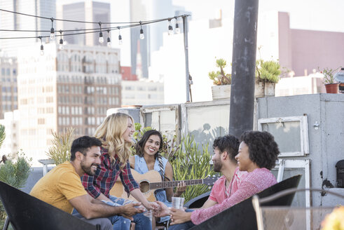 Friends having a rooftop party and playing guitar - WESTF22864