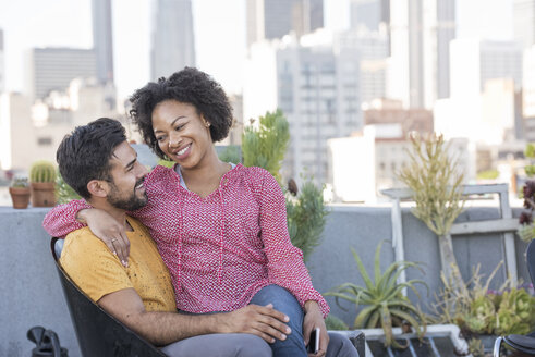 Couple sitting on rooftop terrace - WESTF22867