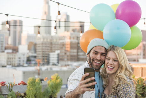 Young couple with balloons standing on rooftop terrace, using smart phone - WESTF22894