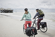 Germany, Schleswig-Holstein, St Peter-Ording, couple riding bicycle on the beach - RORF00709