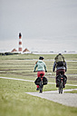 Germany, Schleswig-Holstein, Eiderstedt, couple riding bicycle near Westerheversand Lighthouse - RORF00721