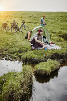 Germany, Schleswig-Holstein, Eiderstedt, couple with bicycles camping in marsh landscape - RORF00736