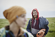 Smiling man with woman in foreground on a trip - RORF00739